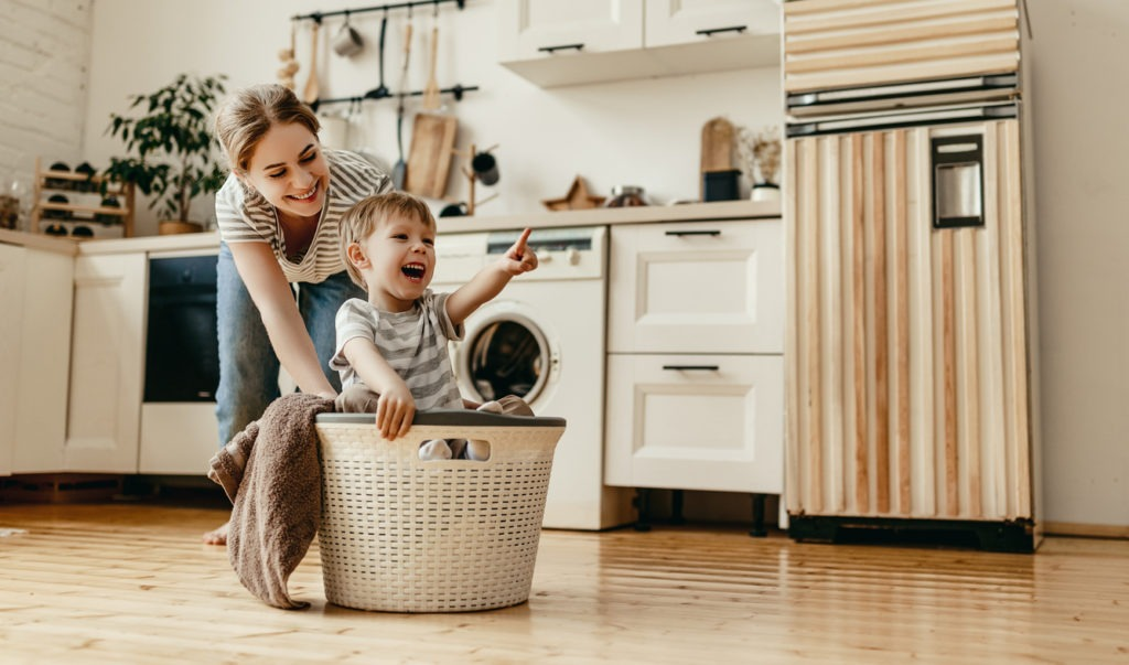 Happy family mother housewife and child son in laundry room